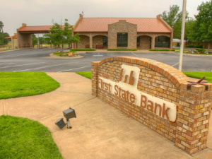 "Bank front with sign reading ""First State Bank"" in beige colored brick."