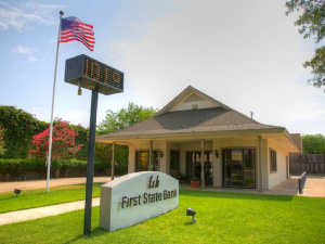 Front of first state bank Throckmorton, american flag on the left and sign out front
